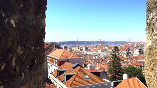 zoom from lisbon castello over the city rooftops towards cristobel and 25 de abril bridge. - 4月25日橋点の映像素材/bロール
