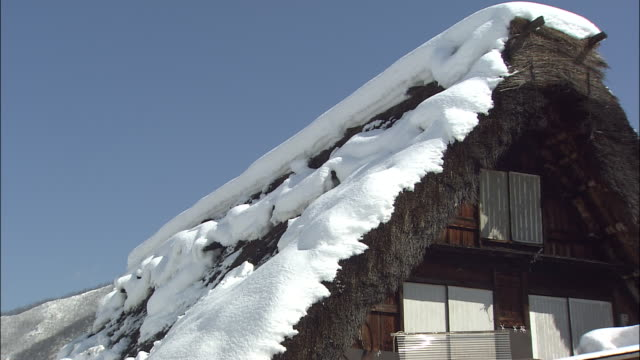 zoom in and pan down snow on thatched roof of gasshozukuri house (the thatched roofs are made to prevent snow accumulating), shirakawago, gifu, japan - thatched roof stock videos & royalty-free footage