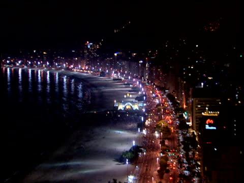 zoom in and pan left across copacabana beach illuminated at night - copacabana stock videos & royalty-free footage