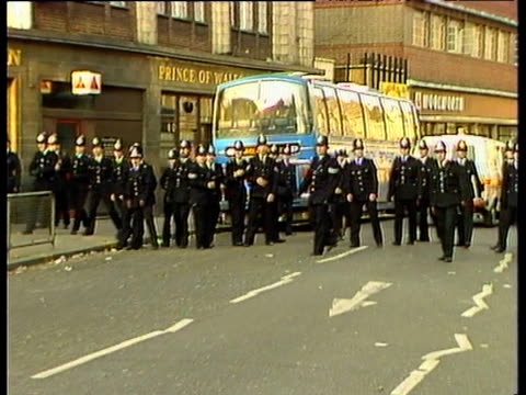 vídeos de stock e filmes b-roll de zoom in and pan right as police officers in uniform form line across coldharbour lane during rioting brixton; apr 81 - 1981