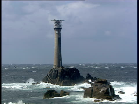 zoom in and track left around longships lighthouse off lands end cornwall - lands end cornwall stock videos and b-roll footage