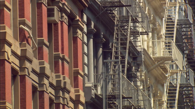 zoom in and zoom out shot of apartment buildings in new york city. - fire escape stock videos and b-roll footage
