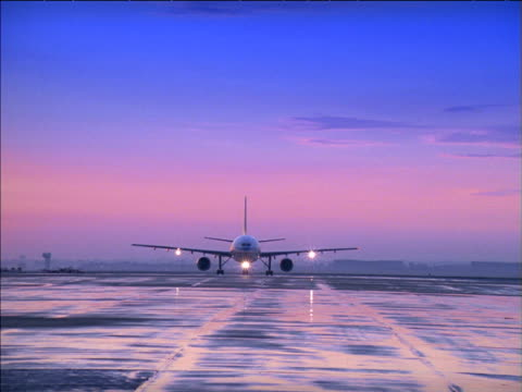 zoom in as aeroplane taxis on wet runway - wet wet wet stock videos & royalty-free footage