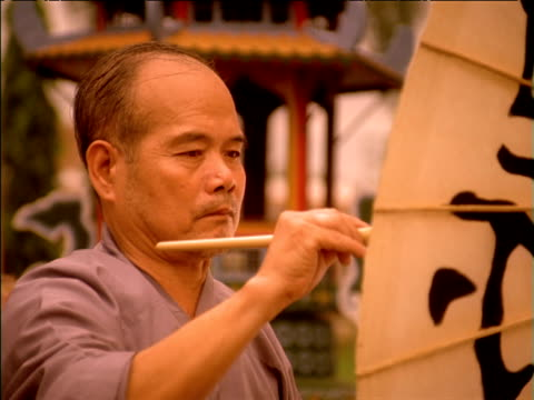 zoom in as man paints chinese characters on bamboo umbrella, china - non western script stock videos & royalty-free footage