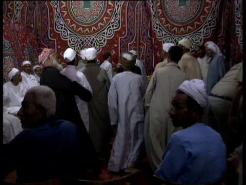 Zoom in as Muslim men perform ritual dance recalling 'Ninety Nine Names of God' during Maulid festival celebrating birth of Prophet Mohammed Cairo