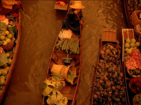 zoom in as woman paddles long boat through floating food market, bangkok - tradition stock videos & royalty-free footage