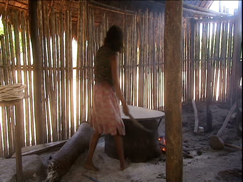 Zoom in as woman scrapes surface of large cassava flat bread cooking on hotplate Amazon Rainforest Venezuela