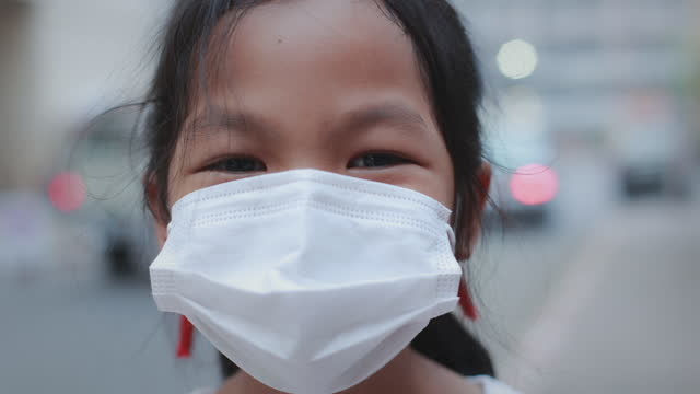 zoom in asian child girl smiling behind the mask and standing in the sidewalk in the city during coronavirus pandemic. - zoom in stock videos & royalty-free footage