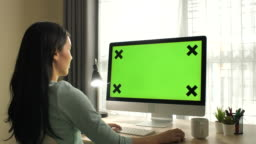 Zoom in Asian Woman Using computer with green screen at home