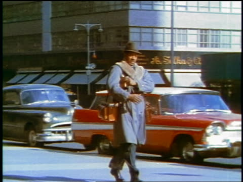 1957 zoom in black businessman in coat + hat with briefcase walking on city street / feature - 書類鞄点の映像素材/bロール