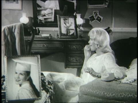 b/w 1962 zoom in blond teenage girl talking on telephone in bedroom - solo adolescenti femmine video stock e b–roll