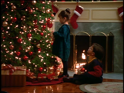 zoom in boy giving christmas ornament to girl who puts it on christmas tree in living room - decorating the christmas tree stock videos & royalty-free footage