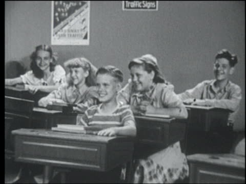 B/W 1949 zoom in boy grinning while sitting at desk in classroom