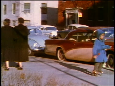 1957 zoom in boy in blue coat roller skating on city sidewalk / feature - 1957 stock-videos und b-roll-filmmaterial