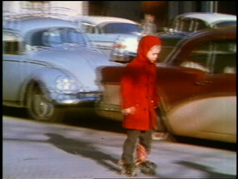 vidéos et rushes de 1957 zoom in boy in red coat roller skating on city sidewalk / feature - 1957