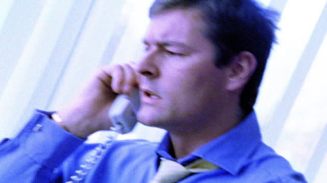 BLUE SELECTIVE FOCUS MS zoom in businessman at desk talking on telephone looking stressed
