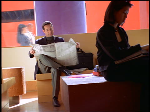 canted zoom in businessman sitting + reading newspaper in waiting room / he takes calculator out - one mid adult man only stock videos & royalty-free footage