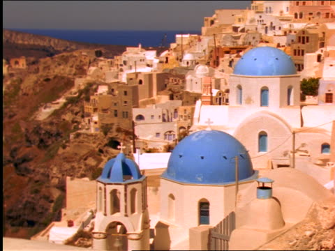 zoom in churches with blue domes / houses on hill + sea in background / oia, santorini, greece - イア点の映像素材/bロール