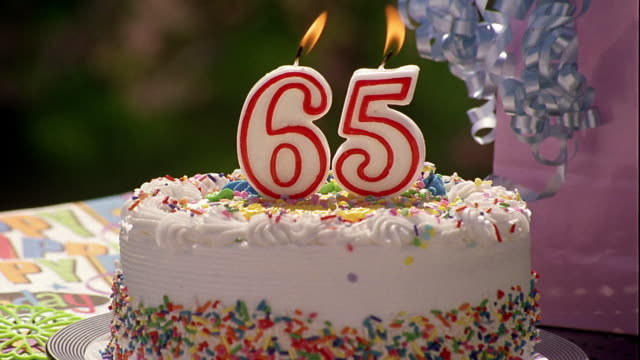 Zoom In Close Up Cake With Numeric Candles For 65th Birthday Burn Before Being Blown Out Stock Footage Video