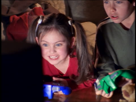 zoom in close up pan girl + boy holding gamepads playing (offscreen) videogame in family room - zoom in stock-videos und b-roll-filmmaterial