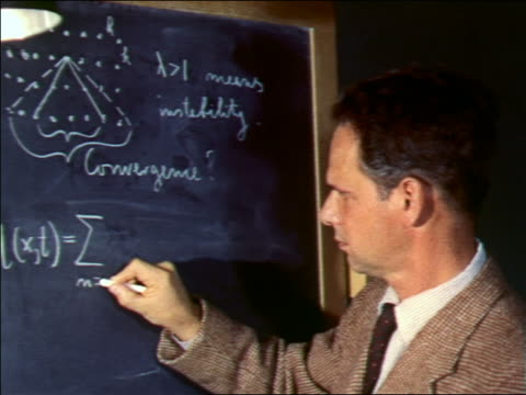 vidéos et rushes de 1956 zoom in close up man writing equations on chalkboard - professor