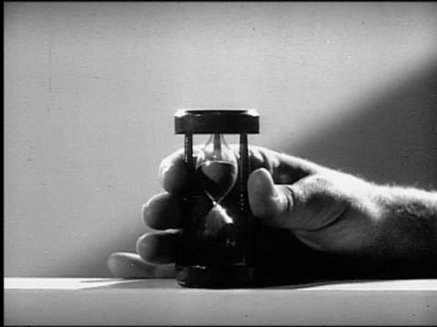 vidéos et rushes de b/w zoom in close up man's hand turning over hourglass on table - limite