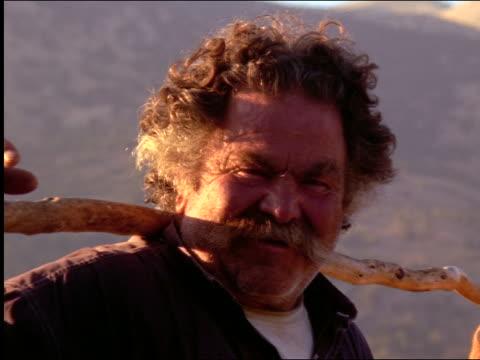 vidéos et rushes de zoom in close up portrait senior male shepherd with staff on shoulders looking at camera / crete, greece - moustache