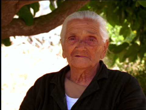 zoom in close up portrait senior woman standing under tree looking + smiling at camera / crete, greece - greece stock videos & royalty-free footage