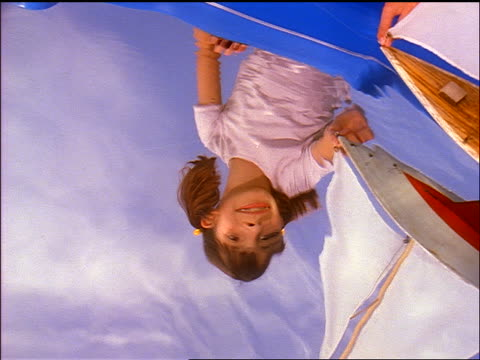 zoom in close up reflection of hispanic girl playing with toy sailboat in water - 船の一部点の映像素材/bロール
