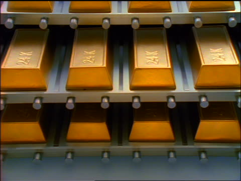 zoom in close up rows of 24k gold ingots sitting on metal trays / bottom tray moves out - lingotto video stock e b–roll