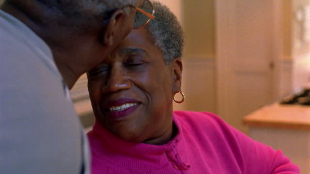 Zoom in close up senior Black man kissing woman on forehead then rubbing heads with her as they smile
