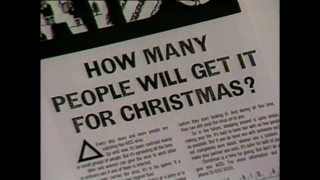 zoom in close up shot of a uk government press campaign advert to raise aids awareness over christmas period, including text ''aids: how many people... - alertness stock videos & royalty-free footage