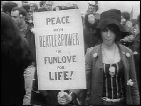 b/w 1967 zoom in close up teen hippy girl with sign at antiwar demonstration in central park / nyc / newsreel - peace demonstration stock videos and b-roll footage