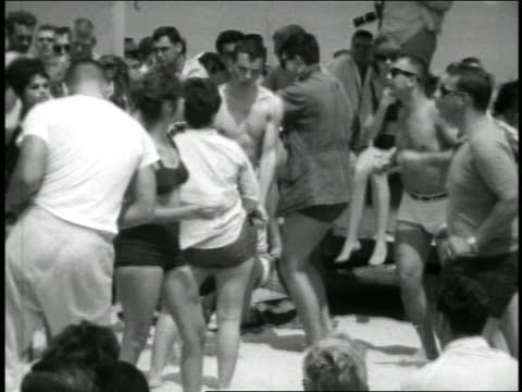 b/w 1967 zoom in crowd doing twist on beach / travelogue - bikini stock-videos und b-roll-filmmaterial