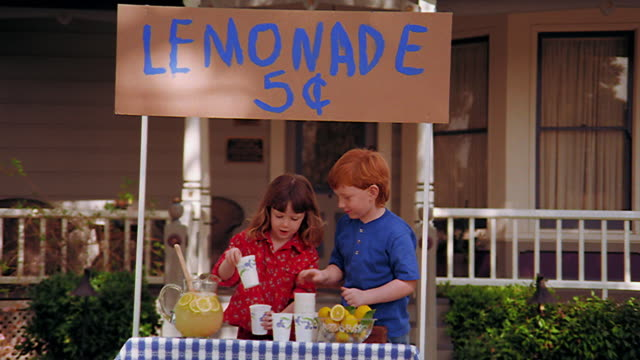 zoom in dolly shot girl + redheaded boy setting up paper cups at lemonade stand in front of house - traditional lemonade stock videos & royalty-free footage