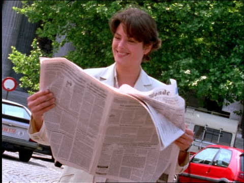 vídeos de stock e filmes b-roll de zoom in european businesswoman laughing + reading newspaper on city street - trabalhadora de colarinho branco