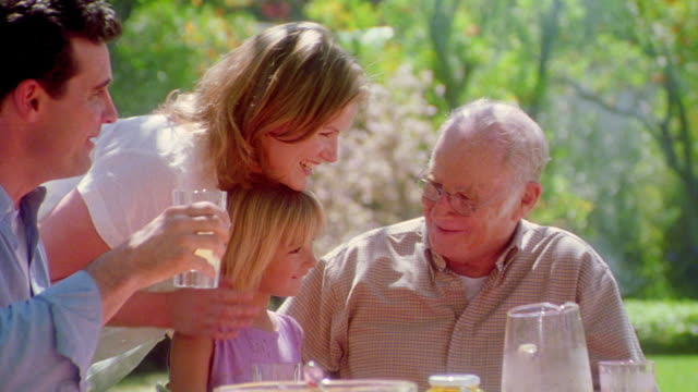 zoom in family picnic / senior man kissing blonde girl next to couple smiling + talking - ピクニック点の映像素材/bロール