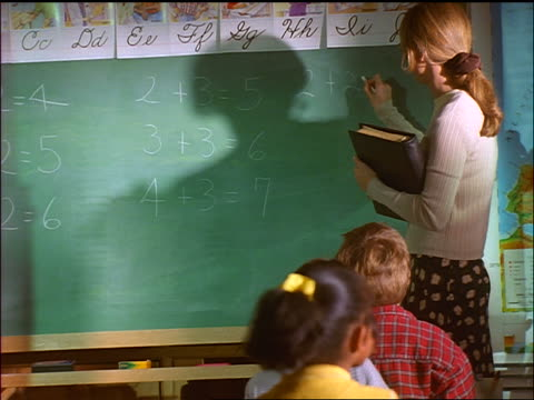 vidéos et rushes de zoom in female teacher writing arithmetic problems on chalkboard in classroom as children raise hands - niveau primaire