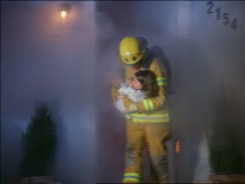 vídeos de stock e filmes b-roll de pan zoom in fireman walking out of burning house carrying girl in nightgown - bombeiro