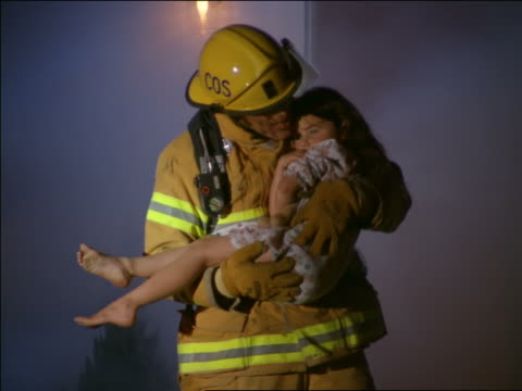vídeos de stock e filmes b-roll de zoom in fireman walking out of burning house carrying girl in nightgown - resgate