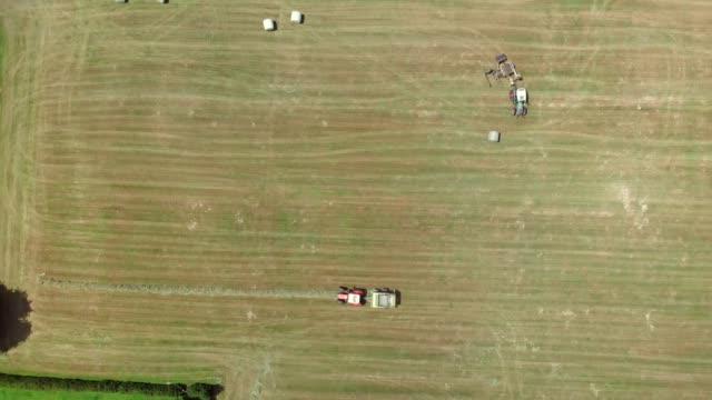 zoomen sie in aufnahmen von landmaschinen, die auf einem feld arbeiten - cereal plant stock-videos und b-roll-filmmaterial
