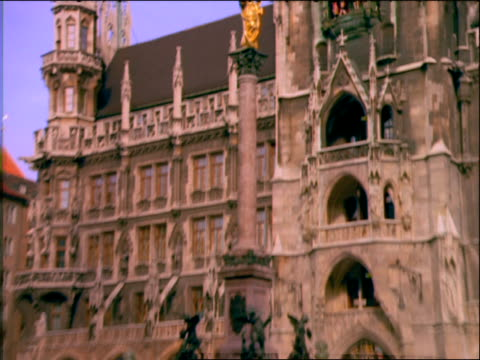 zoom in from crowds in the marienplatz to figures on rathaus / munich - rathaus点の映像素材/bロール