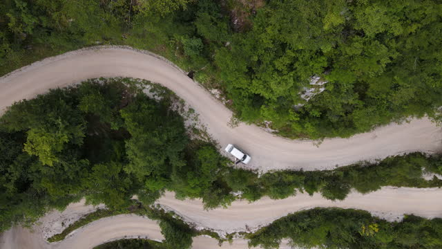 vídeos de stock, filmes e b-roll de zoom in de diretamente acima de um carro estacionado na winding country road - estrada rural