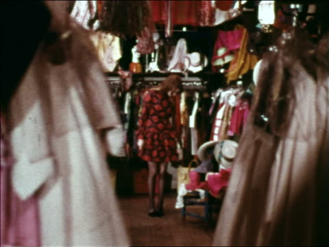 1969 zoom in from hand moving clothing on rack to woman trying on dress in store as saleswoman watches