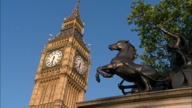 vidéos et rushes de zoom in from low angle shot of clock tower and statue of boudica at 6:30 a.m. / london, england - angleterre