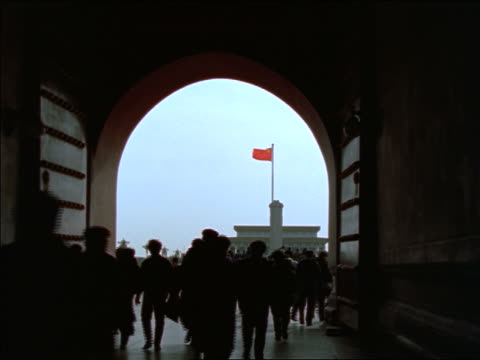zoom in from silhouette of crowd walking through gateway to chinese flag in tiananmen square / beijing - 中国の国旗点の映像素材/bロール