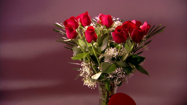 Zoom in from Valentine¿s candy and a bouquet of roses to a close-up of a single red rose.