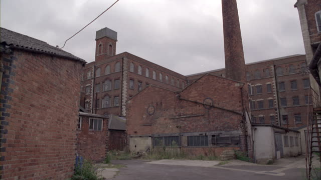 zoom in from wide angle of brick factory or warehouse. smokestack visible in fg. abandoned or rundown industrial area and building. camera zooms in to warehouse window. overcast sky.