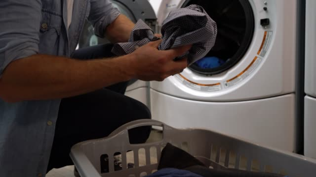 zoom in if unrecognizable customer at a laundromat loading the washing machine - launderette stock videos & royalty-free footage