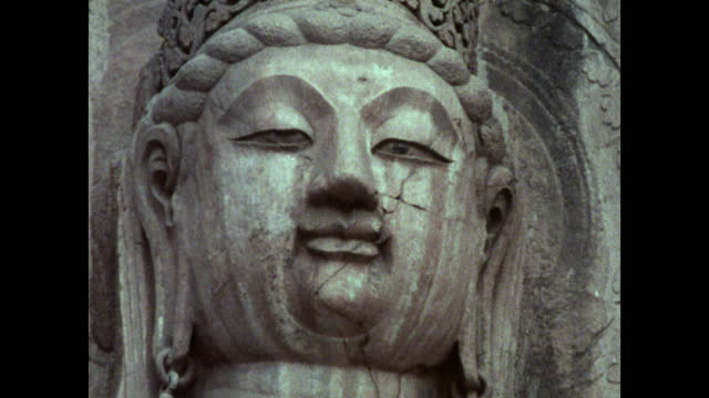 zoom in large bodhisattva statue carved into rock; 1973 - unesco world heritage site stock videos & royalty-free footage